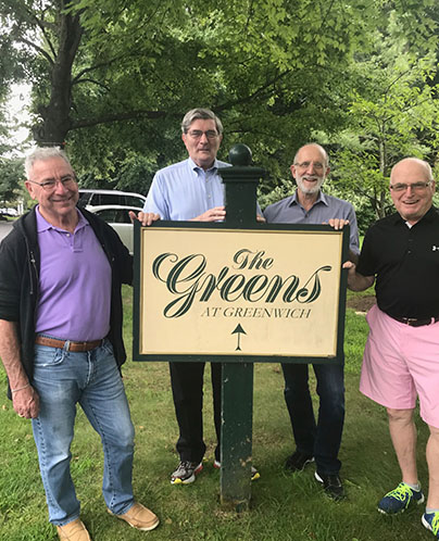 Four men holding the Greens at Greenwich sign.